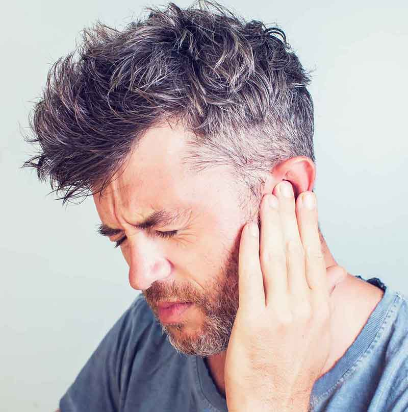 Man experiencing tinnitus (ringing in the ears)